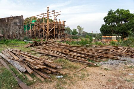 Timber piles and wooden construction frame of an old demolished rice mill in Thailand.