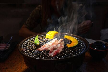 Red raw beef with corn, pumpkin and roselle on charcoal grill with smoke.