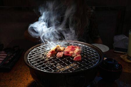Carne de res cocida y cruda a la parrilla de carbón con humo blanco.