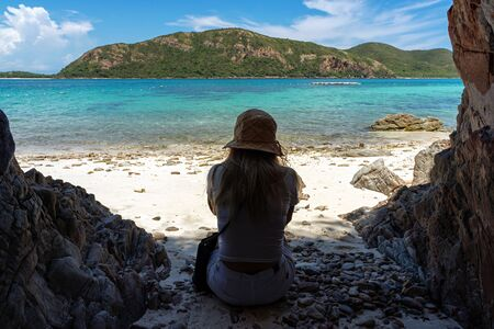 Woman with hat sitting on sand beach under shade with clear turquoise sea and island background.