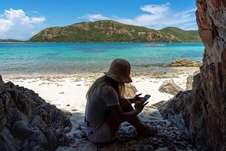 Asian woman sitting using smartphone on sand beach of remote island under the shade with clear turquoise sea background. 写真素材