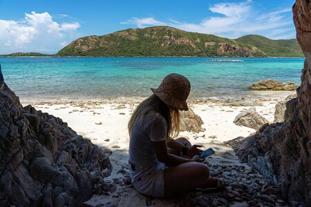 Asian woman sitting using smartphone on sand beach under shade with turquoise sea and island background.