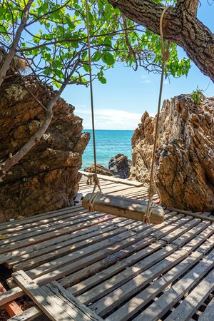 Wooden swing and planks under shade of trees with large rocks and blue sea. 写真素材
