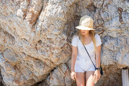 Asian woman wearing straw hat standing under shade of large rock on a bright sunny day.