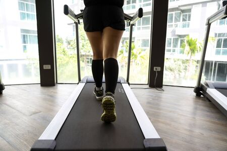Asian female legs running on an indoor treadmill with bright building in the background.