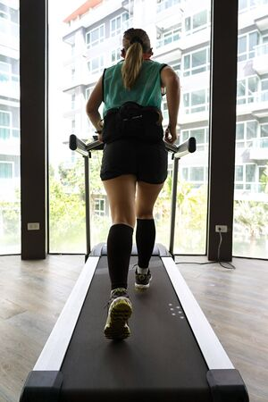 Asian female wearing hydration belt running on an indoor treadmill with bright buildings in the background.