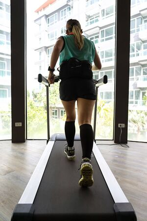 Asian female wearing hydration belt running on indoor treadmill with bright buildings in the background.