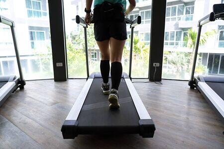 Asian woman jogging on indoor treadmill with bright buildings in background.