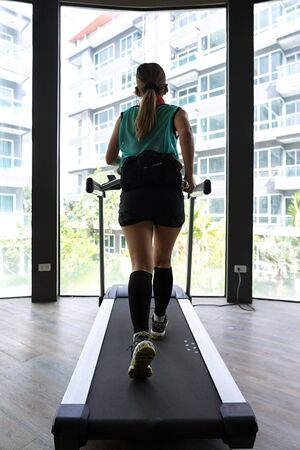 Asian woman with hydration belt running on indoor treadmill with bright building in the background. Stock fotó