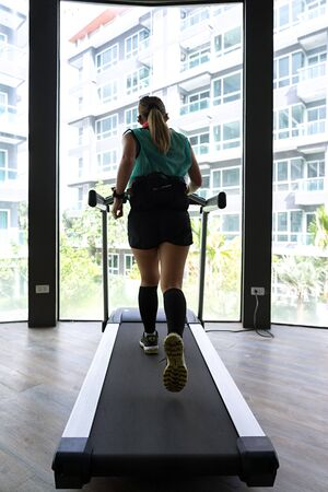 Asian woman with hydration belt running on indoor treadmill with building in the background.