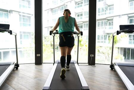 Asian woman wearing calves compression walking on a treadmill with bright buildings in the background.