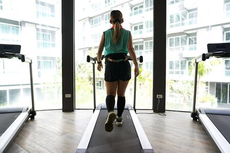 Asian woman wearing headphones walking on a treadmill with bright buildings in the background. Stock fotó