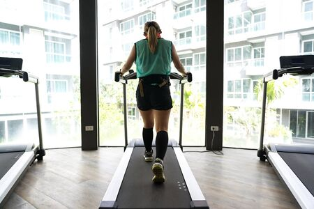 Asian woman walking on a treadmill with bright buildings in the background.