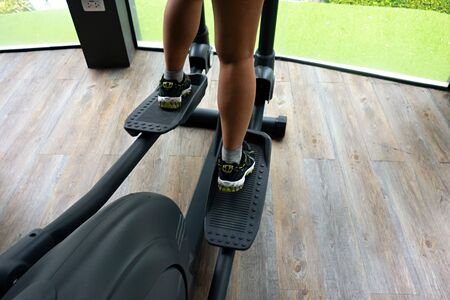 Female legs using elliptical trainer on wooden floor with green grass in background. Stock fotó