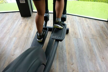 Female legs using elliptical trainer in the gym with wooden floor and green grass in the background. Stock fotó