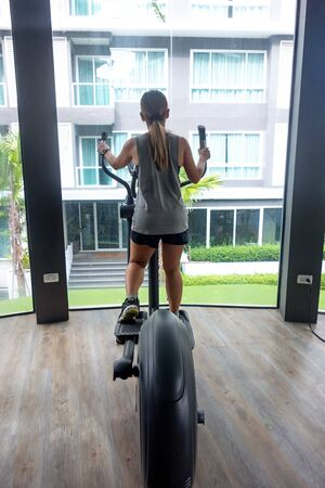 Asian woman using elliptical trainer with bright building in the background.