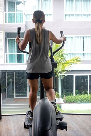 Asian female in sportswear using elliptical trainer in the gym with bright building in the background.
