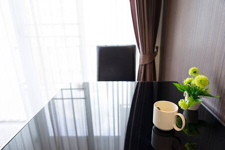 White coffee cup on black glass table with green plastic flowers and bright curtain background.