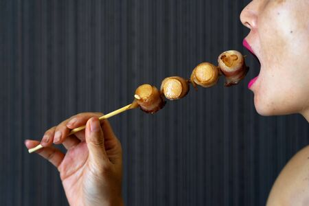 Pink Asian female mouth eating grilled bacon wrapped sausage skewer on dark background.