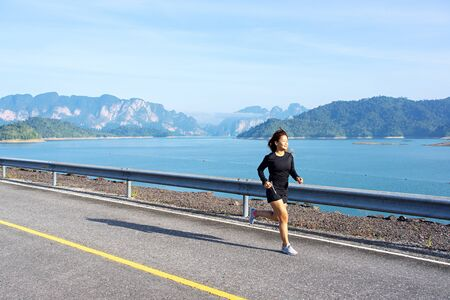 Asian woman running on asphalt road with limestone mountains and lake in the background at Rajjaprabha Dam in Suratthani, Thailand.