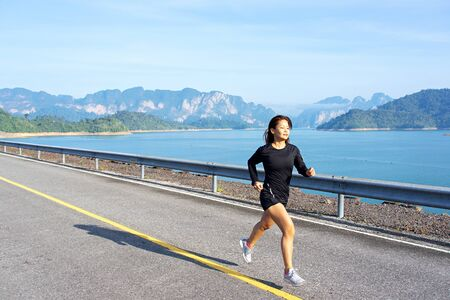 Asian woman runs on asphalt road with mountains and lake in the background at Rajjaprabha Dam in Suratthani, Thailand.