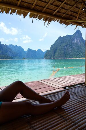 Limestone mountains and lake view from bamboo raft house with relaxing female legs in Surat Thani, Thailand.