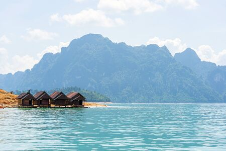 Bamboo raft houses on the lake with limestone mountain range and bright sky background.