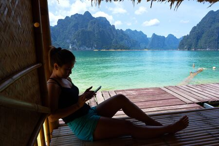 Asian woman sitting using smartphone on bamboo raft house with lake and limestone mountain background in Cheow Lan lake in Surat Thani, Thailand. 版權商用圖片