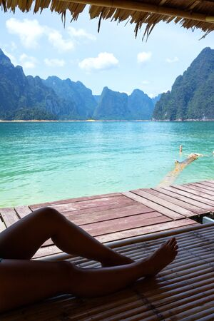 Female legs sitting and relaxing on bamboo raft with lake and limestone mountain range background in Surat Thani, Thailand.