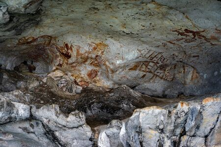 Ancient cave paintings on the limestone wall under an island in Phang Nga Bay, Thailand.