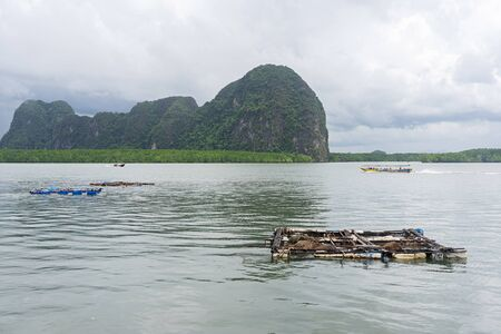 Small aquaculture netting in the sea with limestone island and small boat in the background at Koh Panyee island in Phang Nga, Thailand.