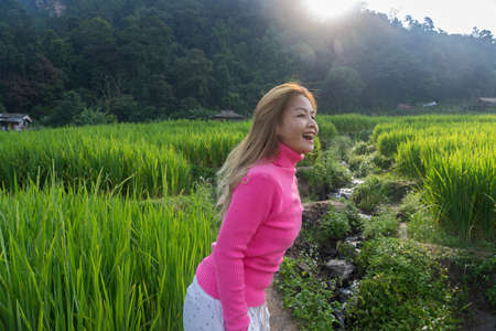 Asian woman in pink sweater walking happily in the green rice field with mountain background in Chiang Mai, Thailand.