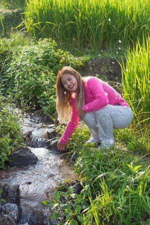 Asian woman splashing water from small stream in the green rice field. 版權商用圖片