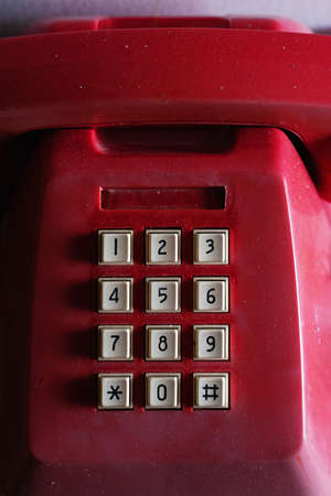 Old red telephone with white numeric pads covered with dust.