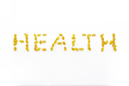 Health letter, A word from beautiful yellow Cod liver oil Omega 3 gel capsules isolated on white background