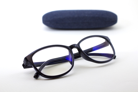nearsighted: Black retro glasses with blue jeans texture case on white background Stock Photo