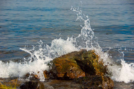 Waves breaking on the shore with sea foam  Stock Photo