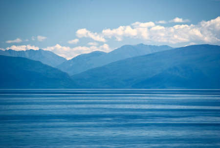 Lake landscape with mountains and water, in blue tones