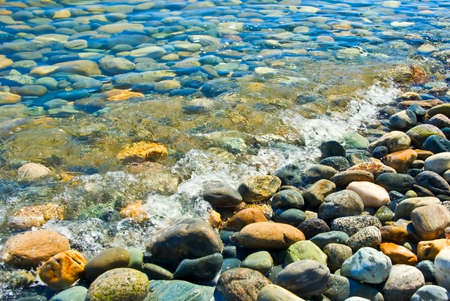 The stones on the beach, visible through the clear water