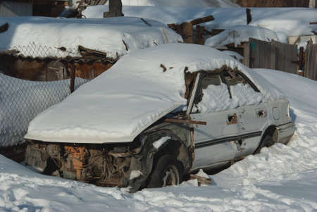 Car without a bumper buried under snow