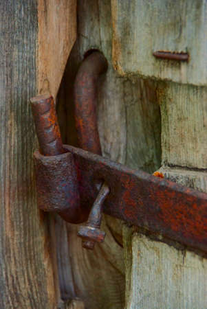 The old rusty latch on a wooden door