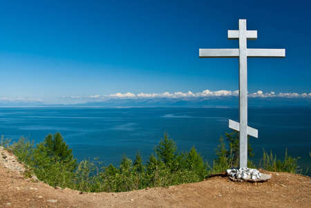 Orthodox cross standing on a hill against a blue sky and water, lake Baikal  Russia  Stock Photo