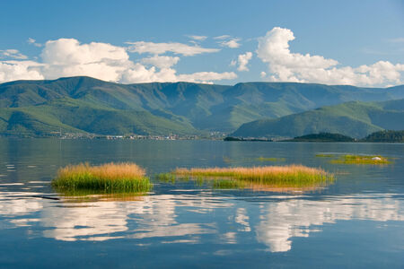 Clouds and mountains reflected in the water surface of the lake Stock Photo