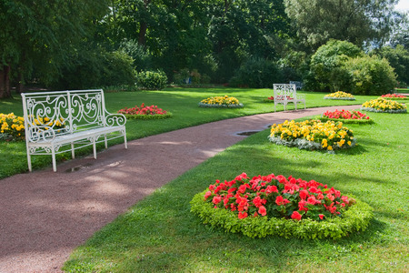 garden bench: Openwork benches among  flowerbeds in a park. Stock Photo