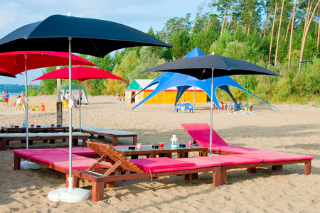 Outdoor beach cafe with sunbeds under umbrellas Stock Photo