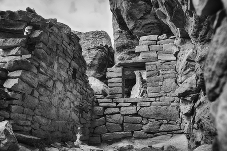 Looking into the remains of an Ancestral Puebloan room. Part of an ancient pueblo in Canyons of the Ancients National Monument. A  black and white photograph of the Anasazi culture recorded in the style of the turn of the century explorers who first found