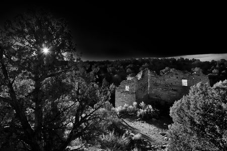 A dramatic turn of the century style photograph of Cutthroat Castle in Hovenweep National Monument. A striking view of the ancient building with early morning sunlight lighting the interior. A dark, moody photograph. Фото со стока