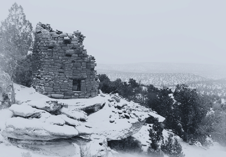 Painted Hand Tower, an Anasazi ruin, overlooking Hovenweep Canyon during a snow storm. A  black and white photograph of the Anasazi culture recorded in the style of the turn of the century explorers who first found these ancient ruins. Фото со стока