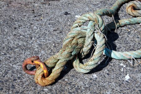 nautic: Old thick rope with rusty metal ring