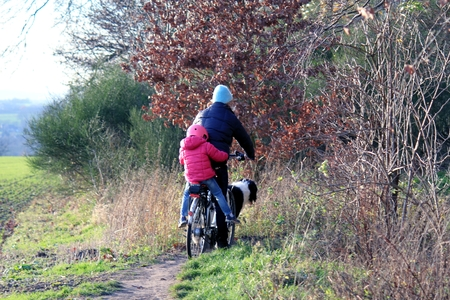 helmet seat: Woman with child on a bicycle from behind in nature